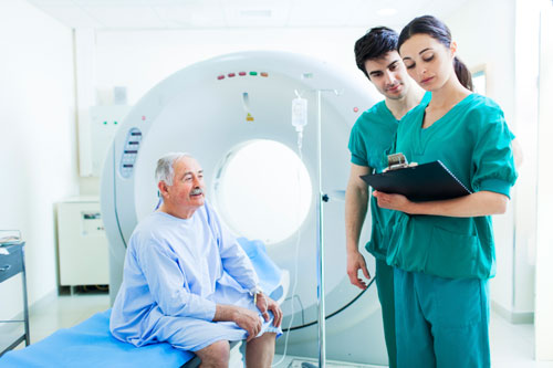Radiologic technologists review a medical chart before performing a computed tomography (CT) exam.