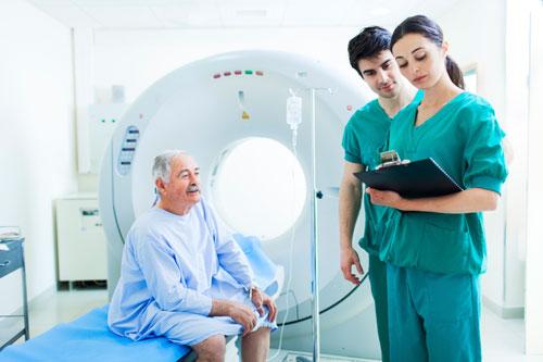 Técnicos radiólogos revisan un informe médico antes de realizar un examen por tomografía computarizada (TAC).