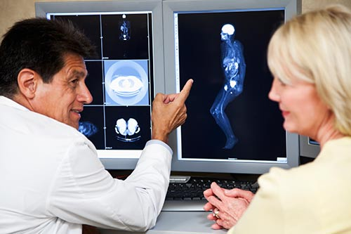 Radiologist and patient reviewing magnetic resonance images.