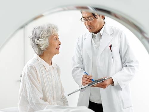 Radiologist preparing patient for magnetic resonance imaging (MRI) exam.