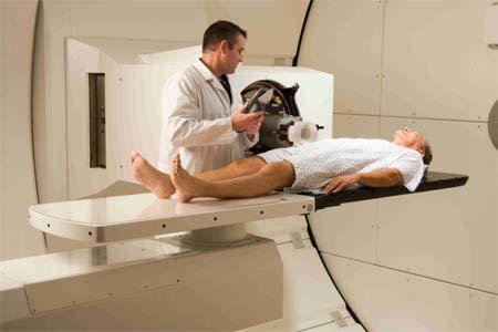 Procedimiento de terapia por protones - paciente en sala de tratamiento con gantry.