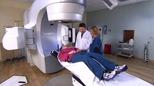 Radiologist and radiologic technologist prepping patient for radiation therapy treatment.