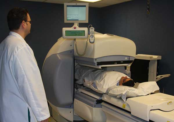 Photograph of a technologist performing a renal scan on a patient using a gamma camera.
