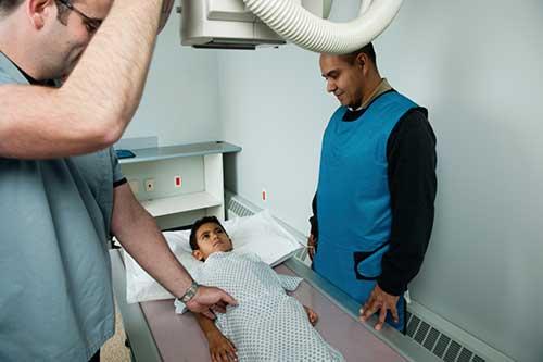 Radiotecnólogo preparando a un paciente para los rayos X.